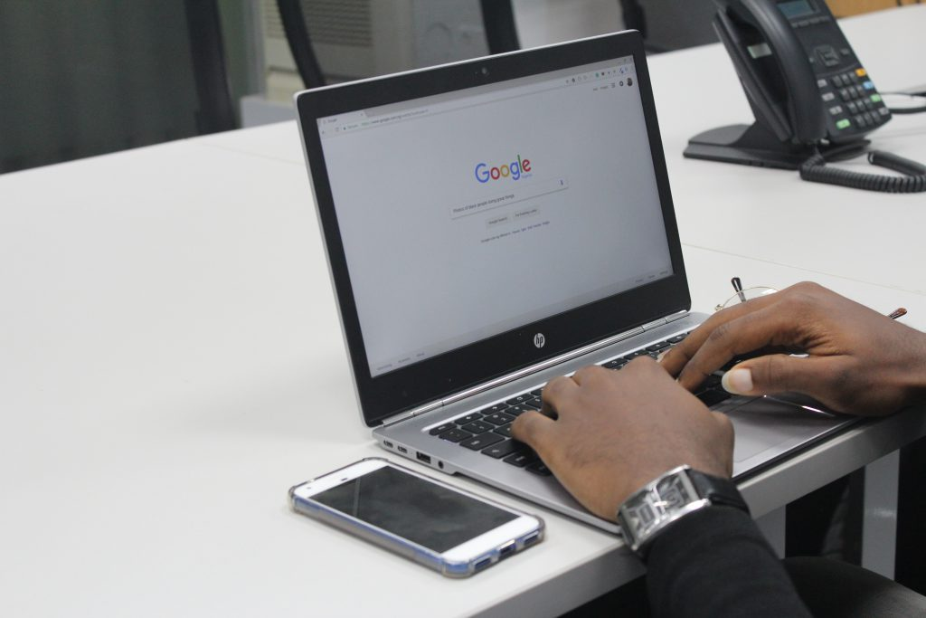 Hands doing a Google search on a laptop.