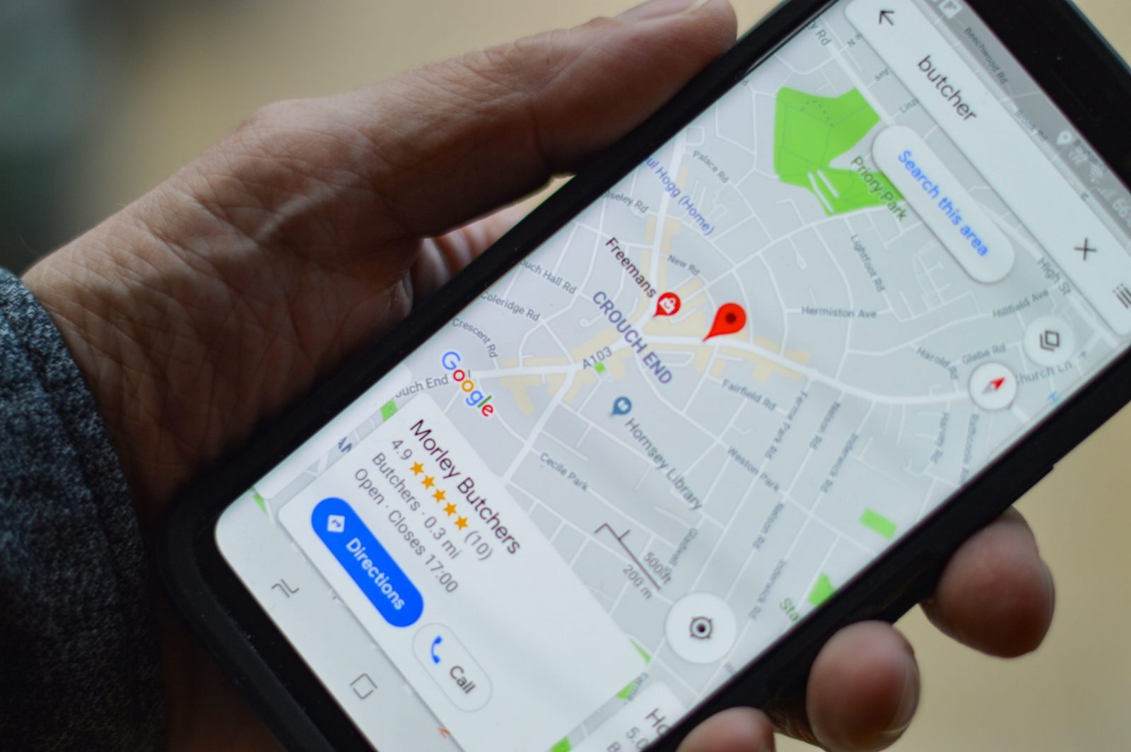 Photo of a phone showing a Google My Business listing on Google Maps.